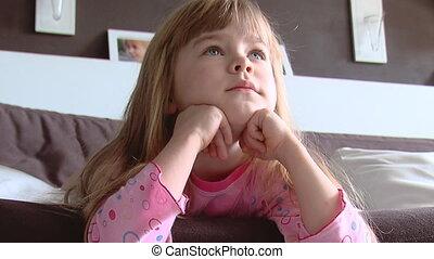 Little girl dreams on a sofa