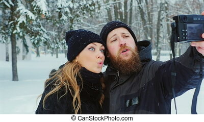 Bearded man and a beautiful woman making selfie
