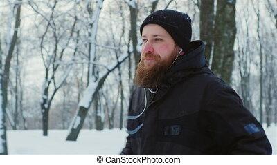 Bearded man jogging in the winter park