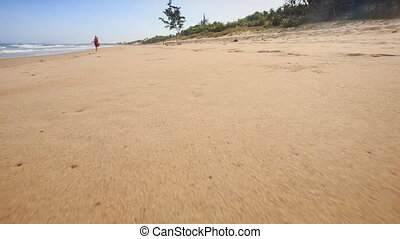 Camera Moves along Footprints Left on Wet Sand - closeup...