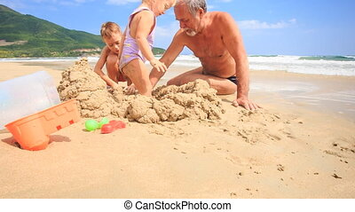 Grandpa Kids Build Sand Castle on Beach by Wave Surf -...