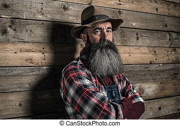 Vintage worker man with long gray beard in jeans dungarees....