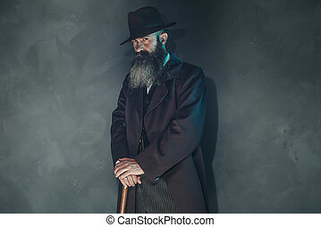 Mysterious vintage beard man in 1900 style fashion with cane...