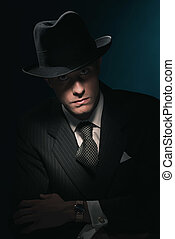 Retro mysterious gangster with hat in suit and tie. Against...