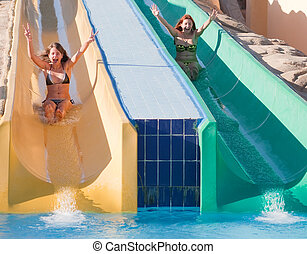 girls in swimming pool water slide at aquapark