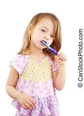 Child Brushing Teeth - Cute little girl in pink pajamas is...