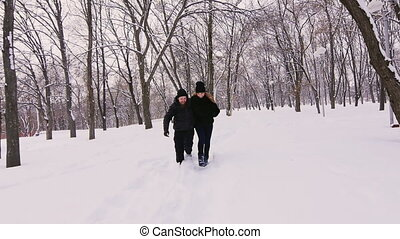 Winter fun - couple walking on snow-covered path and laughs