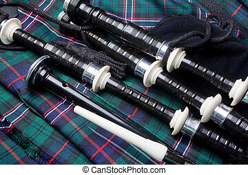 Bagpipes on kilt - Scottish bagpipes lying on a traditional...