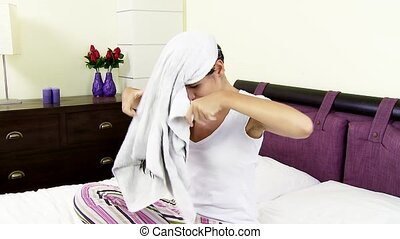 Cute woman drying hair in bedroom - woman in bed drying long...