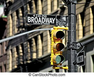 Broadway street sign and traffic light - city building...
