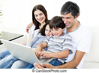 Glad family using a laptop sitting on sofa at home