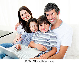 Jolly family at home using a laptop