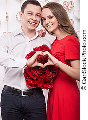Beautiful young couple in love with a bouquet flowers showing the form of heart hands. Valentine's Day.