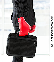 Close-up of a businessman holding a briefcase with boxing gloves in a company
