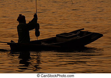 silouette of fisherman in fishing boat on water