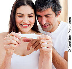 Blissful couple finding out results of a pregnancy test in...