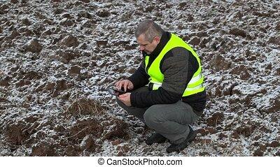 Farmer using tablet PC on frozen field