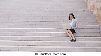 Pretty young worker sitting on steps with laptop - Pretty...