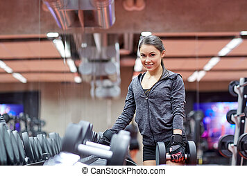 smiling young woman choosing dumbbells in gym - fitness,...