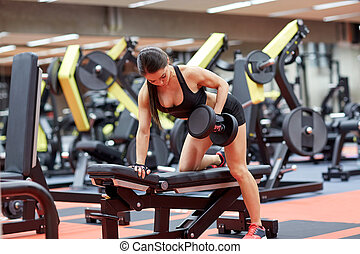 young woman flexing muscles with dumbbell in gym - sport,...