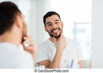 happy young man looking to mirror at home bathroom - beauty,...