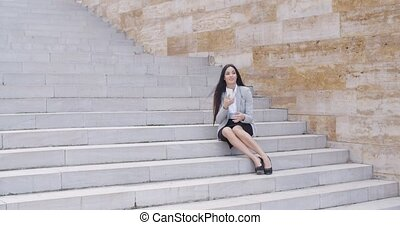 Happy executive with phone and seated on stairs - Single...