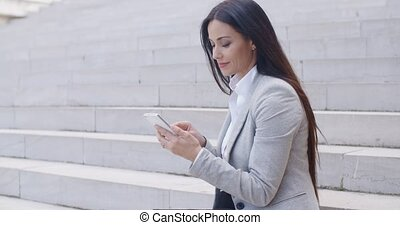 Pretty young worker sitting on steps with phone - Pretty...