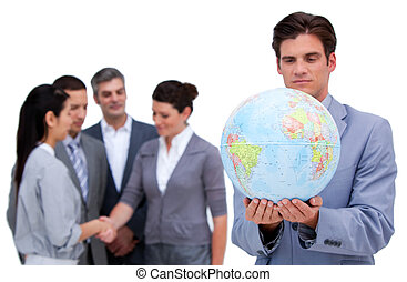 Handsome business man and his team looking at a terrestrial globe against  a white background