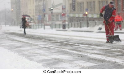 Woman walking on frozen pavement during snow storm - Adult...