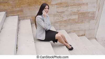 Cute business woman sitting on steps with phone - Top view...