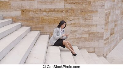 Pretty business woman sitting on steps using phone - Side...