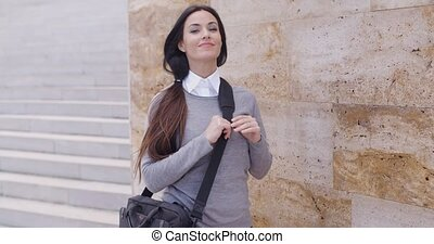 Grinning woman in sweater near wall looking over - Grinning...