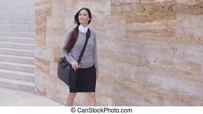 Gorgeous business woman walking past wall - Gorgeous young...