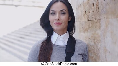 Confident young woman leaning against wall