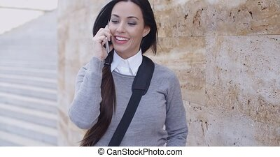 Laughing woman in sweater near wall on phone - Laughing...