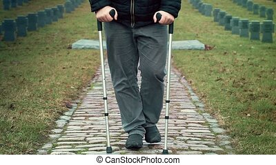 Disabled veteran on crutches walking away at cemetery