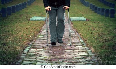 Disabled veteran on crutches walking at cemetery