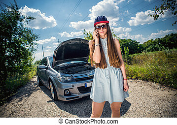 Young woman near broken car speaking by phone needs...