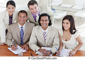 Cheerful business team in a meeting smiling at the camera