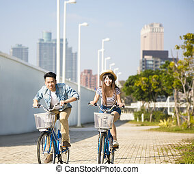 happy young couple riding on bicycle in city park