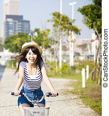happy young woman riding on bicycle in city park