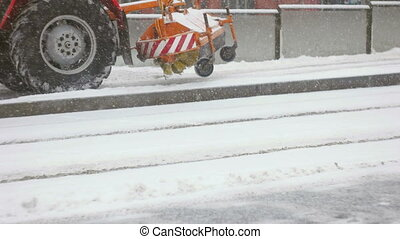 A tractor cleaning up fresh snow from the platform - Side...