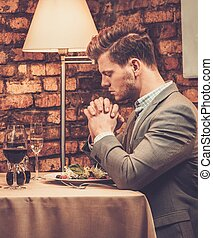 Stylish wealthy man pray before meal at restaurant