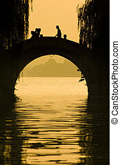 hangzhou - silhouette of people walking on the bridge in...