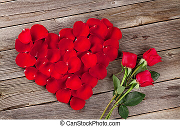 Red rose petals heart and flowers over wooden table. Top...