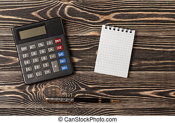 Pen, notebook and calculator on wooden background