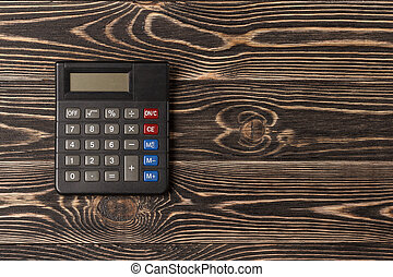 Small personal calculator on wooden background. Flat design.