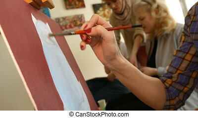 Female artist paints picture artwork in art studio - Female...
