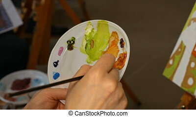 Graphic artist mixing oils color paints in palette with...