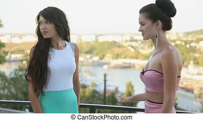 Attractive models in dresses posing on the outdoor terrace...